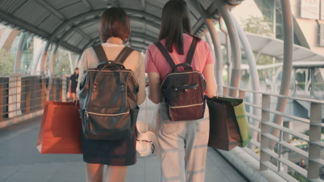 vídeos de stock e filmes b-roll de two female tourists walking with shopping bags,slow motion - carrying