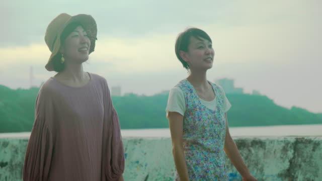 two female walking - 談笑する点の映像素材/bロール