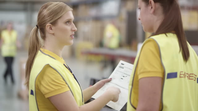 two female warehouse employees discussing a document one is holding - polo shirt stock videos & royalty-free footage