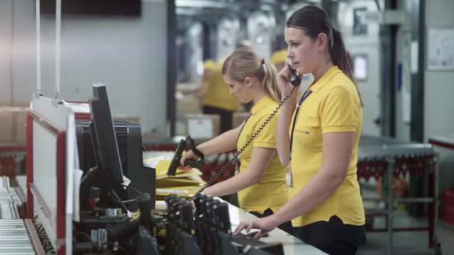 two female warehouse employees working at the office desk in the warehouse - telephone receiver stock videos & royalty-free footage