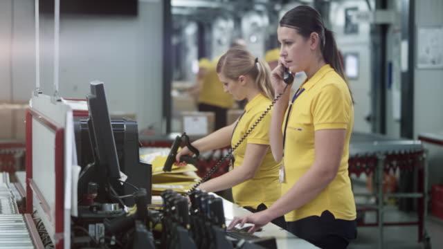 stockvideo's en b-roll-footage met twee vrouwelijke magazijnmedewerkers werken bij het bureau in het magazijn - telefoonhoorn