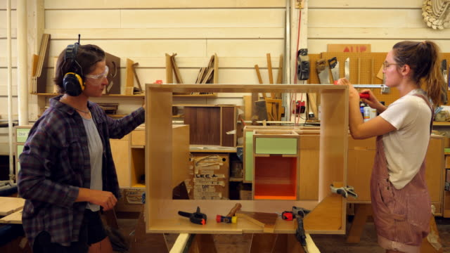 MS Two female woodworkers assembling cabinet together in woodshop