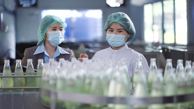 two female worker in bottling factory checking bottles before shipment - surgical cap stock videos & royalty-free footage
