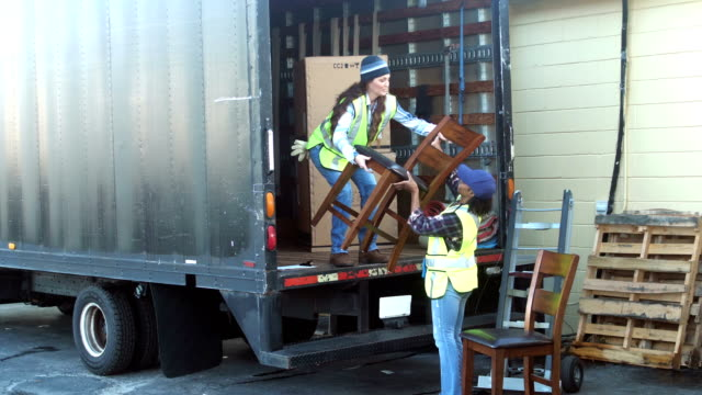 two female workers loading furniture onto delivery truck - removal man stock videos & royalty-free footage