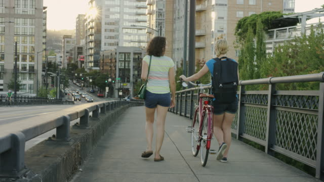 Two female young adults talking and walking across bridge with bike