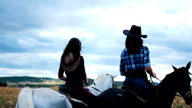 vídeos de stock, filmes e b-roll de duas fêmeas, andar a cavalo para a frente - montar um animal