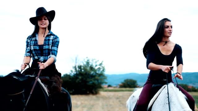vídeos de stock, filmes e b-roll de duas fêmeas, andar a cavalo, um deles é inquieto - montar um animal