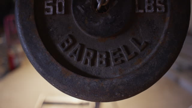 two fifty pound iron bar bell weights swing on a chain toward and away from camera in a workshop. - exercise equipment stock videos and b-roll footage