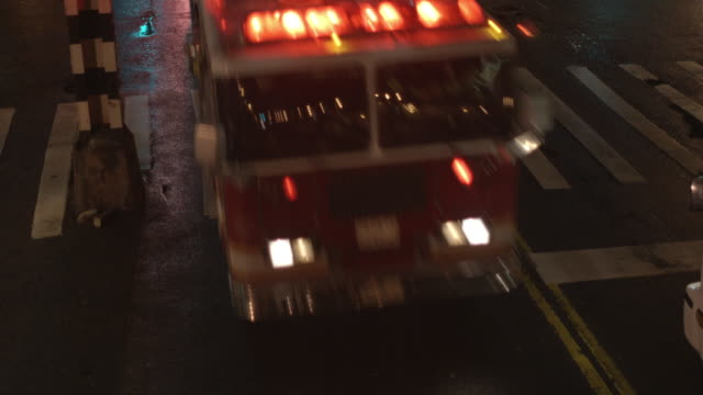 vídeos de stock e filmes b-roll de cu, ha, two fire trucks driving on street at night, new york city, new york, usa - carro de bombeiro