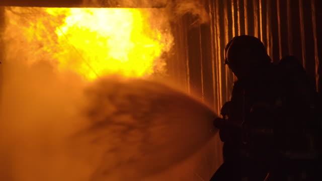 vídeos y material grabado en eventos de stock de dos bomberos de servicio en el edificio quema.dos bomberos luchando contra un incendio con una manguera y agua durante un tiroteo. - incendios provocados