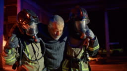 Two firefighters carrying a man out of the burning building at night
