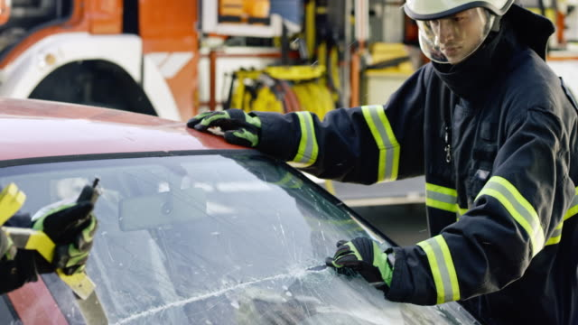 two firefighters cutting the windshield of a car - firefighter stock videos and b-roll footage
