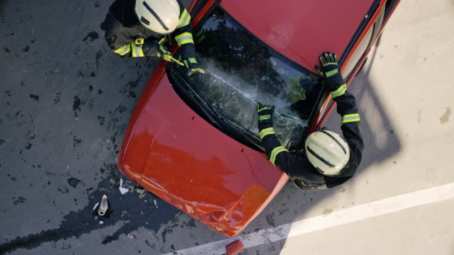 cs two firefighters cutting through the windshield of a car in an accident - traffic accident stock videos & royalty-free footage