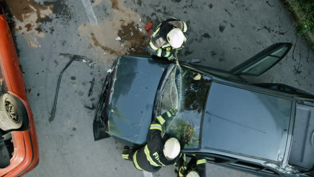 cs two firefighters cutting through the windshield of a crashed car at the scene of a car accident - incidente automobilistico video stock e b–roll