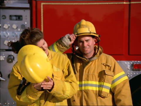 MS PORTRAIT two firefighters standing in front of fire truck / woman taking helmet off