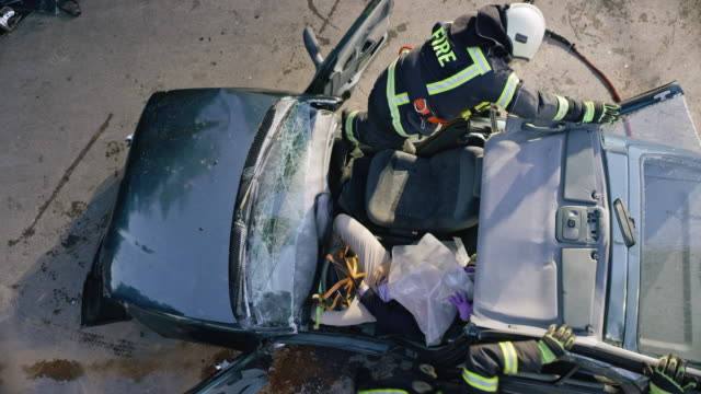 vídeos de stock e filmes b-roll de cs two firefighters taking off the cut roof of a crashed car to get to the injured driver - para brisas