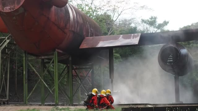 two firefighters training are spraying high pressure water fire fighting operation, - airplane hangar stock videos & royalty-free footage
