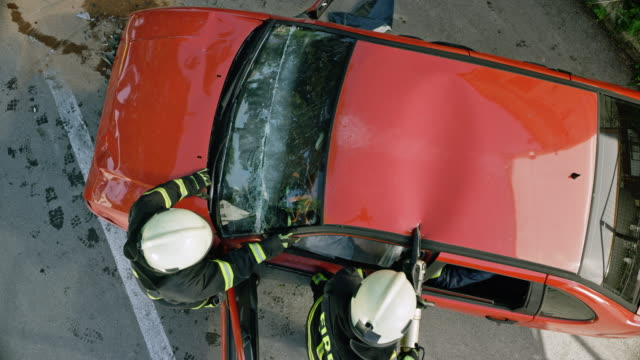 cs two firefighters using a hydraulic cutter to cut the roof of a crashed car - traffic accident stock videos & royalty-free footage