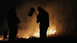 Two firefighters with fire flappers extinguish a fire in the forest at night
