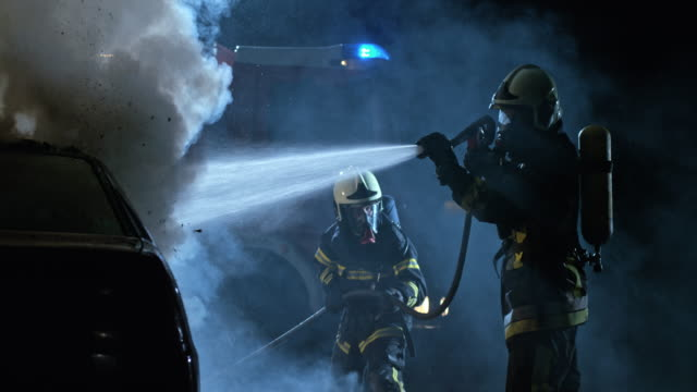 slo mo two firemen putting out a car fire at night - fire hose stock videos and b-roll footage