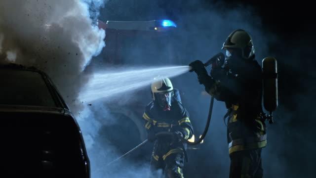 stockvideo's en b-roll-footage met slo mo twee brandweerlieden blussen van een brand auto 's nachts - fire hose