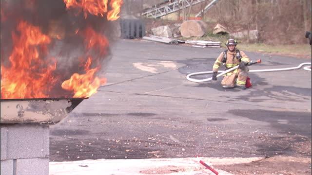 two firemen watch as fuel burns in a metal tub. - brennbar stock-videos und b-roll-filmmaterial