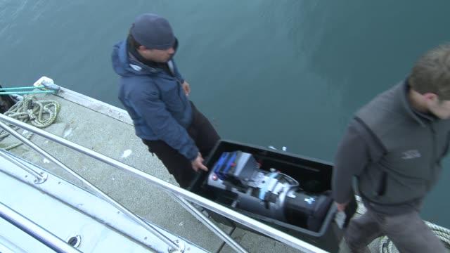 two fishermen carry a tote off a marina dock. - 重い点の映像素材/bロール
