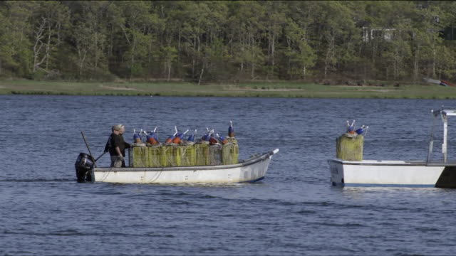 Two fishermen in small skiff loaded with lobster traps pull up alongside bigger lobster boat in harbor