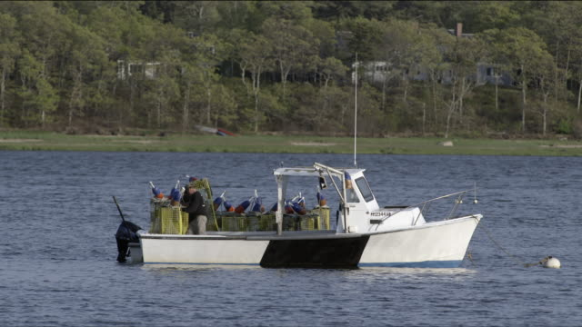 Two fishermen transfer lobster traps from small skiff to bigger lobster boat in harbor