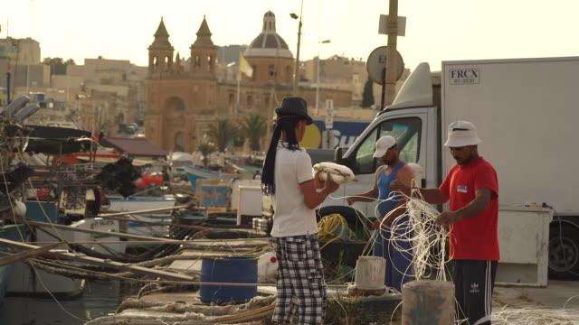 stockvideo's en b-roll-footage met two fishermen working on dock in fishing village - malta - klein