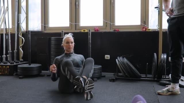 due donne in forma che si allenano con la palla di medicina in palestra - cura della persona video stock e b–roll
