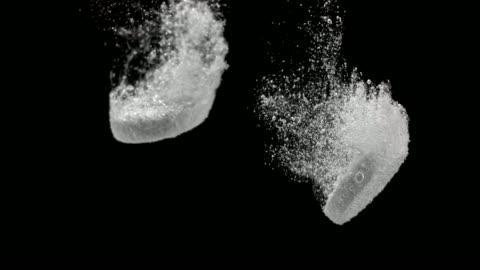 stockvideo's en b-roll-footage met slo mo twee bruisen tabletten ontbinding op zwarte achtergrond - dissolving