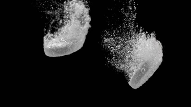 slo mo two fizzing tablets dissolving on black background - dissolving stock videos & royalty-free footage