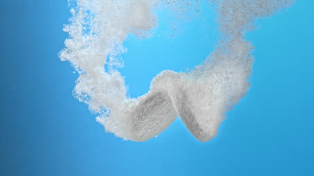 slo mo two fizzing tablets on blue background - dissolving stock videos & royalty-free footage