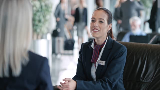 ds two flight attendants talking while sitting in the business lounge at the airport - necktie stock videos and b-roll footage