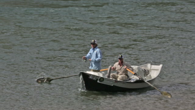 Two fly fishermen float and fish from a drift boat on the Snake River in Idaho