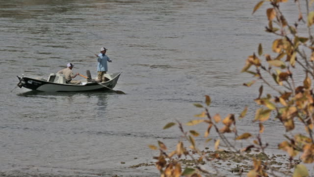 stockvideo's en b-roll-footage met two fly fishermen float and fish from a drift boat on the snake river in idaho - hoofddeksel