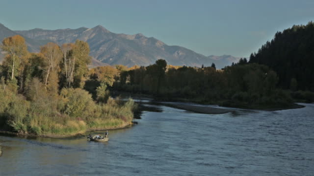 two fly fisherpeople float and fish from a drift boat in the distance on the snake river in idaho - river snake stock videos & royalty-free footage