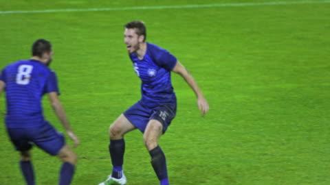 slo mo two football teammates celebrating a goal - möjlighet bildbanksvideor och videomaterial från bakom kulisserna