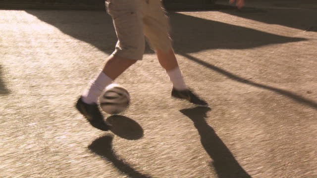 vídeos y material grabado en eventos de stock de ms ts two footballers, one dribbling, london, uk - truco