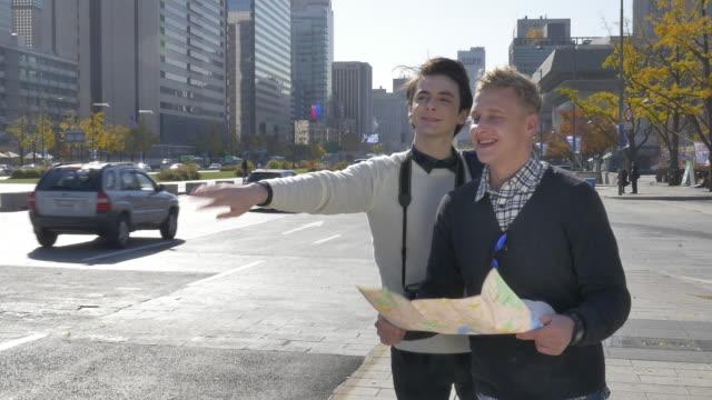 vídeos de stock, filmes e b-roll de two foreign tourists trying to get a taxi on seoul street - braço humano
