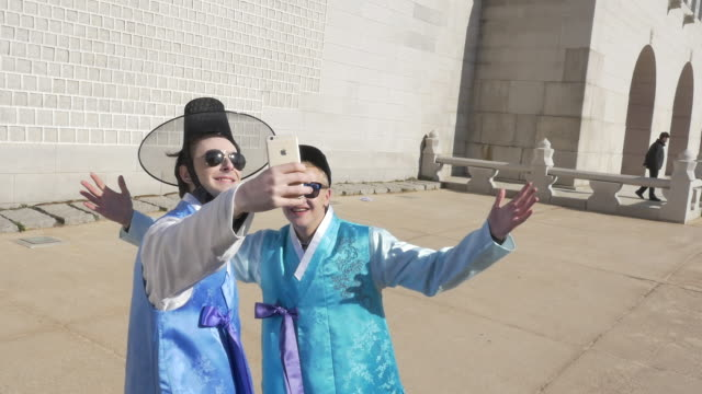 stockvideo's en b-roll-footage met two foreign tourists wearing hanbok (korean traditional attire) taking a selfie - traditie
