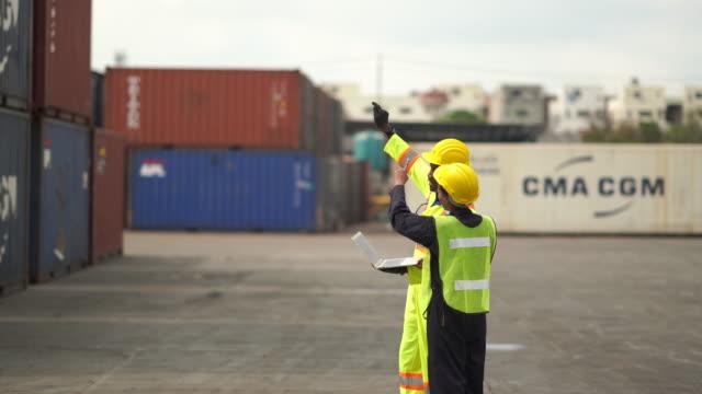 vidéos et rushes de deux foreman contrôlent la boîte de chargement dans le transport maritime d'entrepôt - débardeur