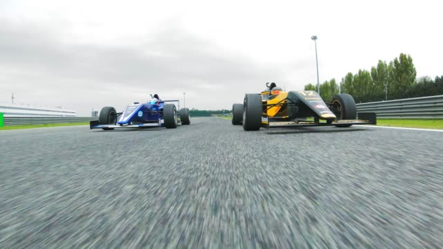 Two formula cars racing each other on the track