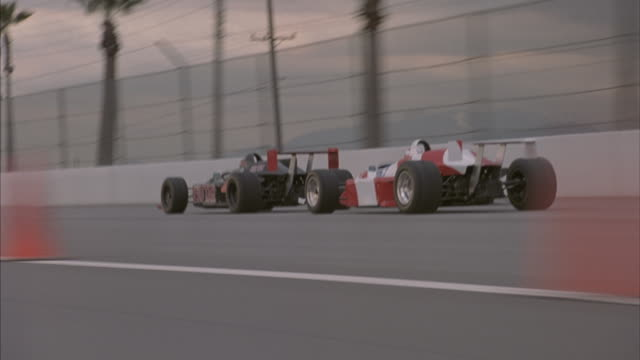 Two Formula One race cars speed around the track at a speedway.