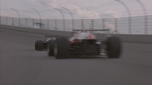 Two Formula-One race cars speed around a turn on a speedway.