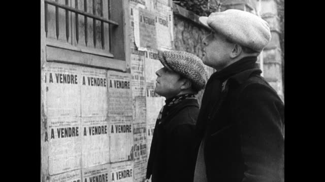 two french farmers standing reading 'a vendre' postings on wall 'a vendre' sign on barn - 1934 stock-videos und b-roll-filmmaterial