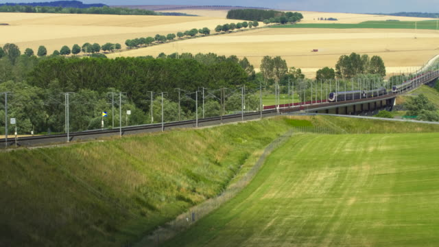 vidéos et rushes de two french high speed tgv trains cross each other on opposite tracks in rolling landscape, meuse department, lorraine - voie ferrée