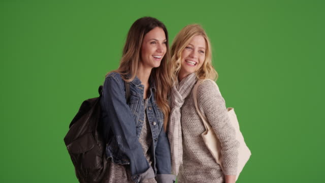 two friendly girls standing laughing and gossiping in front green screen wall. - blond hair stock videos & royalty-free footage