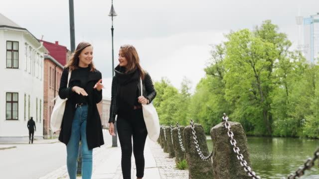 Deux amis marchent dans la ville après qu'ils aient fait des courses d'épicerie som